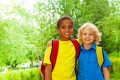 Two happy boys wearing school bags stand together royalty free stock image