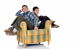 Two happy brothers. Two young happy smiling boys lean on against each others back sitting in the chair Stock Photo