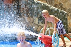 Two happy brothers having fun in aqua park. Two happy teenage boys, sportive twin brothers, having fun together jumping in splashing in outdoors swimming pool in Royalty Free Stock Photography