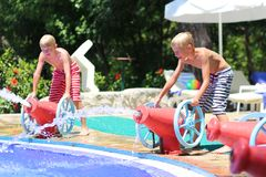 Two happy brothers having fun in aqua park. Two happy teenage boys, sportive twin brothers, having fun together jumping in splashing in outdoors swimming pool in Royalty Free Stock Images