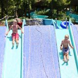 Two happy brothers having fun in aqua park. Two happy teenage boys, sportive twin brothers, having fun together jumping in splashing in outdoors swimming pool in Royalty Free Stock Photos