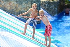 Two happy brothers having fun in aqua park. Two happy teenage boys, sportive twin brothers, having fun together jumping in splashing in outdoors swimming pool in Stock Images