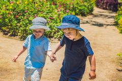 Two happy brothers running together on a park path in a tropical park.  Royalty Free Stock Photography