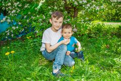 Two happy brothers walk in the Park on a Sunny summer day. Happy family spending time outdoors on a Sunny summer day. Couple giving two young children piggyback Royalty Free Stock Image