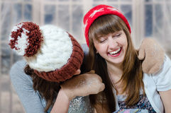 Two happy brunette girls  in winter hats and Royalty Free Stock Images