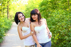 Two happy brunette women in a summer park. Two happy brunette women in  summer park Stock Images