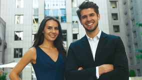 Two happy business partners posing in front of big business center. Two happy business partners posing in front of big building in the street stock footage