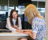 Two happy business women talking and signing credit. Or insurance Royalty Free Stock Image