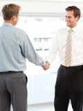 Two happy businessmen concluding a deal. By shaking their hands standing in the office Royalty Free Stock Photo