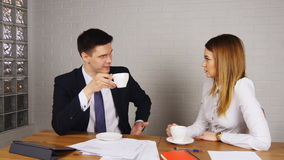 Two happy businesspeople with coffee at office talking stock video