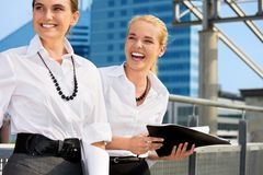 Two happy businesswomen with folders Stock Photo