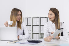 Two happy businesswomen in office with a tablet Stock Photography