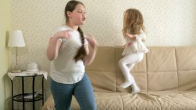 Two happy carefree little girls are dancing and jumping music. 4k stock footage