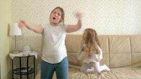Two happy carefree little girls are dancing and jumping music. 4k stock video footage