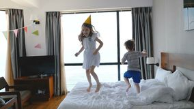 Two happy Caucasian little 5-8 year old kids, brother and sister, cheerfully jumping on bed in a light room, having fun. Happy cute children enjoying leisure stock video footage