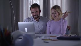 Two happy Caucasian people looking in the laptop and laughing. Man and woman watching funny video or picture online