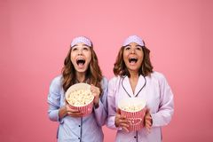 Two happy cheerful girls dressed in pajamas. Holding popcorn and looking up at copy space isolated over pink background Stock Image