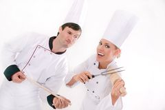 Two happy chefs. Two young chefs having fun with utensils Royalty Free Stock Image