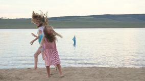 Two happy child on beach play games. Children perform acrobatic stunts tricks. They have fun and jump dancing. Their hair fluttering in the wind stock footage