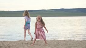 Two happy child on beach play games. Children perform acrobatic stunts tricks. They have fun and jump dancing. Their hair fluttering in the wind stock video