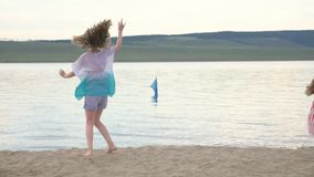 Two happy child on beach play games. Children perform acrobatic stunts tricks. They have fun and jump dancing. Their hair fluttering in the wind stock video footage
