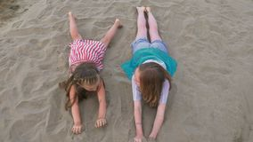 Two happy child on beach play games. Kid roll on the sand and laugh stock video