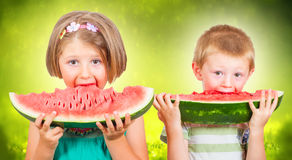 Two Happy child eating watermelon in the garden Stock Images