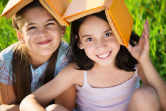Two happy child girls studying on grass Royalty Free Stock Photography