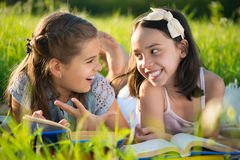 Two happy child girls studying on grass Royalty Free Stock Images