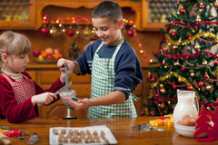 Two happy child preparing cookie for family dinner on Xmas eve Royalty Free Stock Photos