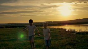 Two happy child running around and jumping in the park. On the field, the two brothers are playing at sunset. The sun stock footage