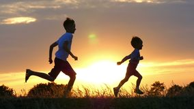 Two happy child running around and jumping in the park. On the field, the two brothers are playing at sunset, the sun stock footage