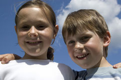 Two Happy Children. Two children outdoors arm in arm on a sunny day with a blue sky in the background Stock Photo