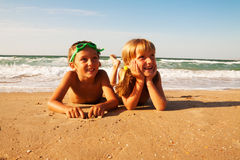 Two happy children on beach, sea in background. Stock Photo