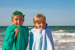 Two happy children on beach, sea in background. royalty free stock image