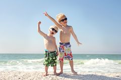 Two Happy Children on Beach Vacation. Two young children are happily holding their arms in the air as they stand on the beach by the ocean on a family vacation Royalty Free Stock Images