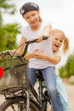 Two happy children on a bicycle Stock Photos