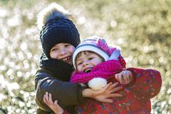 Two happy children boy and girl playing outdoors in sunny winter. Day royalty free stock images