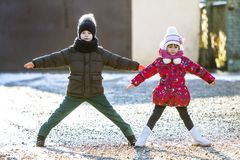 Two happy children boy and girl playing outdoors in sunny winter. Day Royalty Free Stock Photo