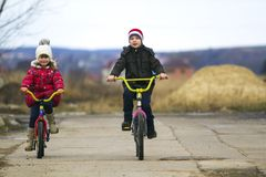 Two happy children boy and girl riding bicycles outdoors in cold. Weather Royalty Free Stock Photos
