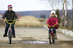 Two happy children boy and girl riding bicycles outdoors in cold. Weather Stock Photos