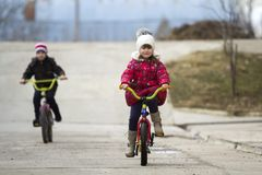 Two happy children boy and girl riding bicycles outdoors in cold. Weather Royalty Free Stock Image