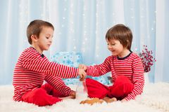 Two happy children eating cookies at christmas and drinking milk Stock Photos