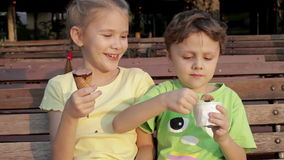 Two happy children eating ice cream. On bench in the park at the day time. Concept healthy food stock video footage