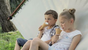 Two happy children eating ice cream in the park at the day time. Concept healthy food stock video footage