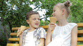 Two happy children eating ice cream in the park at the day time. Concept healthy food stock video