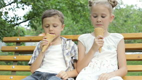 Two happy children eating ice cream in the park at the day time. Concept healthy food stock footage