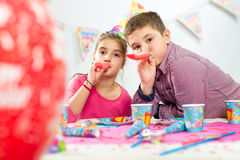 Two happy children having fun at birthday party Stock Photos