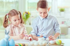 Two happy children having fun during painting eggs for easter in Royalty Free Stock Photography