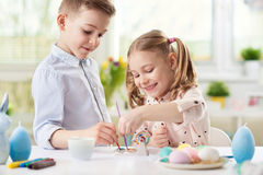 Two happy children having fun during painting eggs for easter in stock images